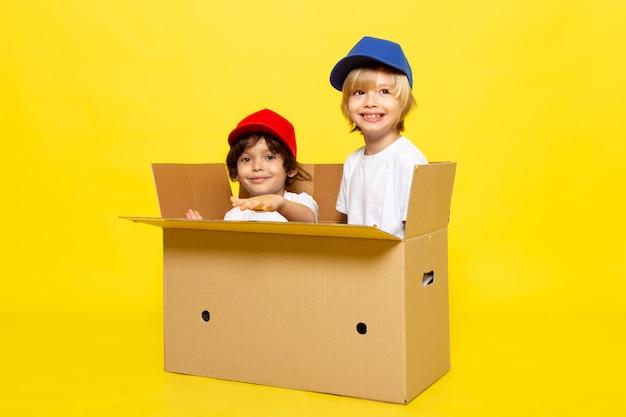 Una vista frontal lindos niños pequeños con camisetas blancas gorras rojas y azules sonriendo dentro de una caja marrón en la pared amarilla