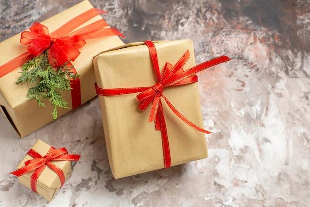 Vista frontal lindos regalos de navidad atados con lazos rojos sobre fondo claro