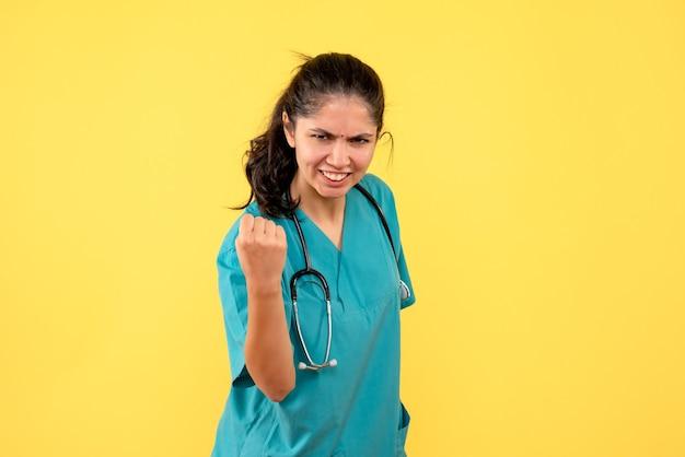 Vista frontal lleno de alegría joven doctora en uniforme de pie sobre fondo amarillo