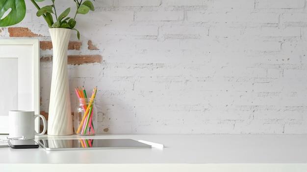 Vista frontal del lugar de trabajo, espacio de copia, tableta, cartel de maqueta en la mesa de loft de espacio de trabajo blanco.