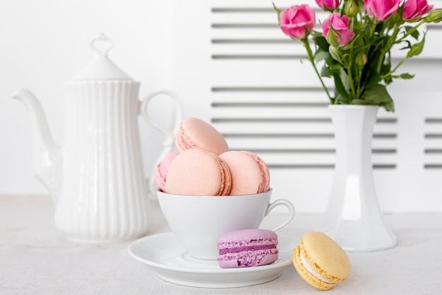 Vista frontal de macarons en copa con rosas en florero