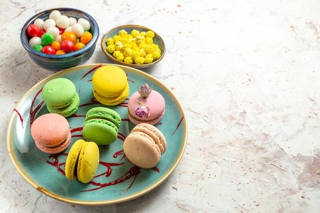 Vista frontal de macarons franceses con caramelos en la galleta de la galleta de la torta del color de la tabla blanca