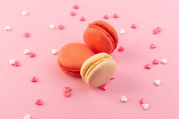 Una vista frontal de macarons franceses de colores formados y deliciosos en el escritorio rosa
