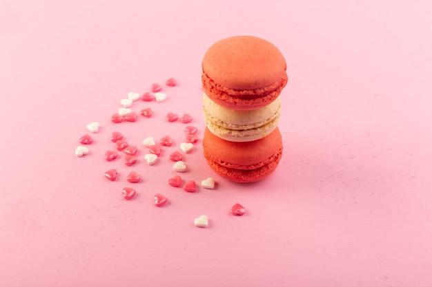 Una vista frontal de macarons franceses de colores redondos formados en el escritorio rosa