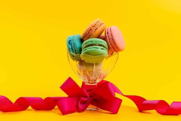 Una vista frontal macarons franceses deliciosos dentro de vidrio redondo aislado en amarillo, pastelería de galletas y pasteles