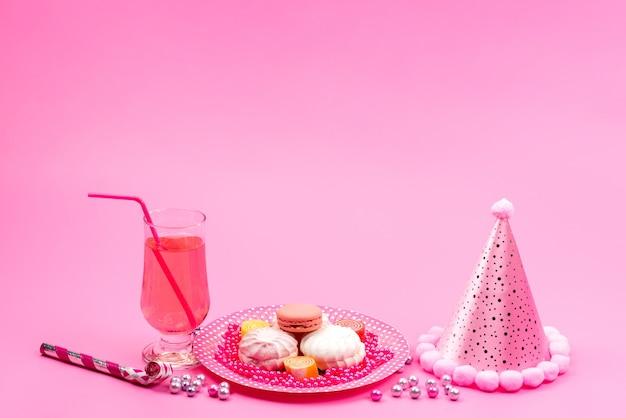 Una vista frontal de macarons franceses dentro de la placa junto con la bebida y la gorra de cumpleaños en rosa, celebración de regalos de fiesta