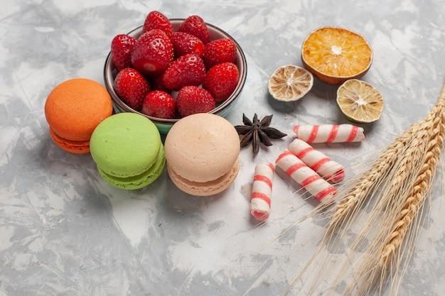 Vista frontal de macarons franceses con fresas rojas frescas sobre superficie blanca