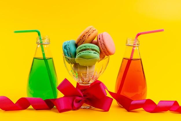 Una vista frontal de macarons franceses junto con bebidas de colores con pajita en amarillo, pastel de galleta dulce