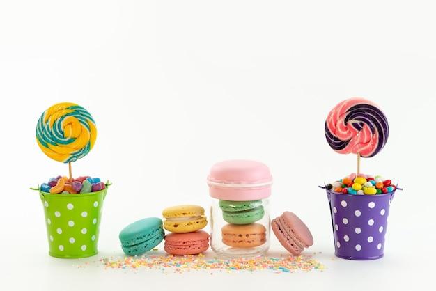 Una vista frontal de macarons franceses junto con caramelos de colores dentro de cestas en blanco, paleta dulce de azúcar de color