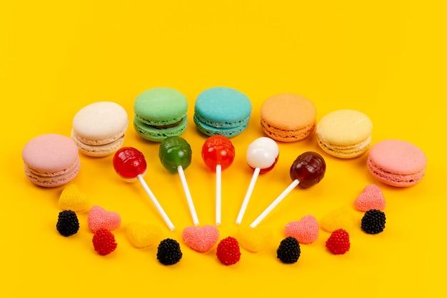 Una vista frontal de macarons y piruletas junto con mermeladas aisladas en amarillo, caramelo dulce de pastel de azúcar