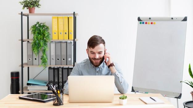 Vista frontal macho adulto disfrutando del trabajo en la oficina