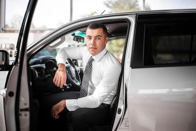 Vista frontal macho dentro del coche con puerta abierta