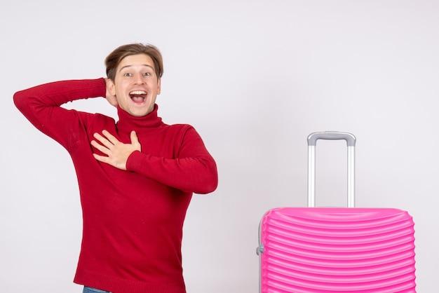 Vista frontal macho joven con bolsa rosa sobre fondo blanco emoción modelo viaje vacaciones vuelo verano color