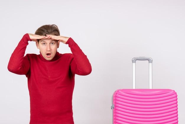 Vista frontal macho joven con bolsa rosa sobre fondo blanco emoción modelo viaje vuelo color vacaciones