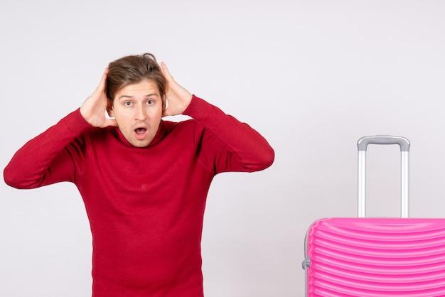 Vista frontal macho joven con bolsa rosa sobre fondo blanco emoción modelo viaje vuelo verano color vacaciones