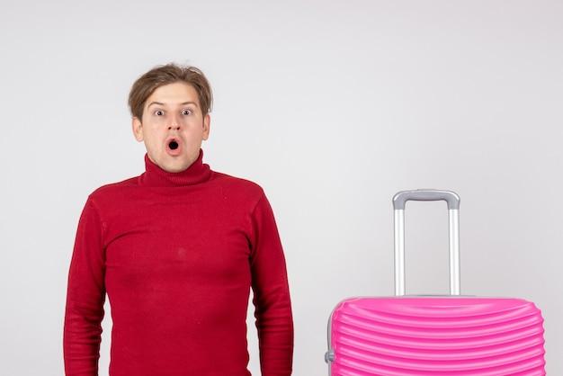 Vista frontal macho joven con bolsa rosa sobre un fondo blanco mar vacaciones color emociones vacaciones viaje de verano