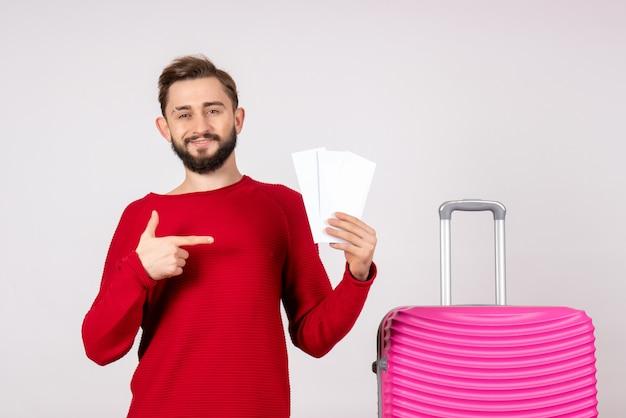 Vista frontal macho joven con bolsa rosa y sosteniendo boletos en la pared blanca color turista de viaje de vuelo de vacaciones