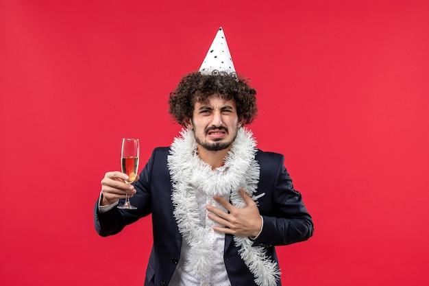 Vista frontal macho joven celebrando el año nuevo que viene en la pared roja fiesta de navidad