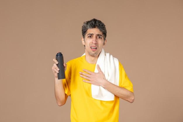 Vista frontal macho joven con espuma y toalla preparándose para afeitarse la cara sobre fondo de color rosa