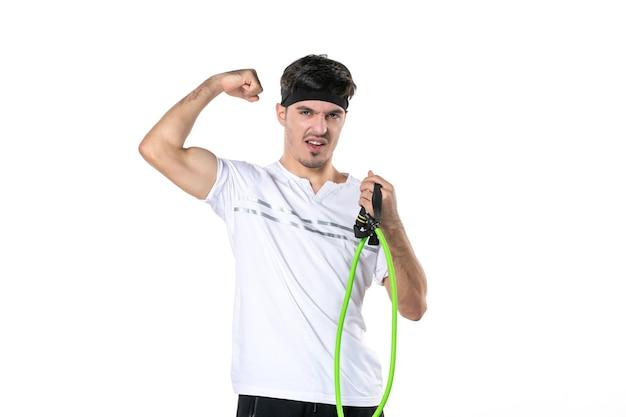 Vista frontal macho joven con expansor en sus manos flexionando sobre fondo blanco régimen ajuste atleta gimnasio entrenamiento estilo de vida cuerpo dieta deporte