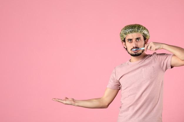 Vista frontal, macho joven, limpieza, el suyo, dientes, en, fondo rosa