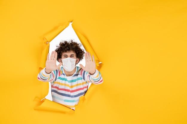 Vista frontal macho joven en máscara blanca estéril en color amarillo rasgado covid- virus pandémico de fotografía humana