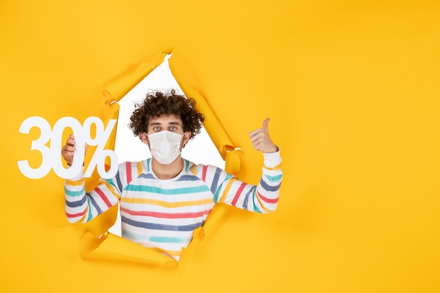 Vista frontal macho joven en máscara sosteniendo en colores amarillos virus de compras salud covid- foto pandemia