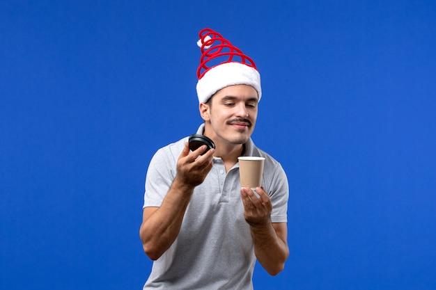 Vista frontal macho joven oliendo café en la pared azul año nuevo emociones de vacaciones masculinas