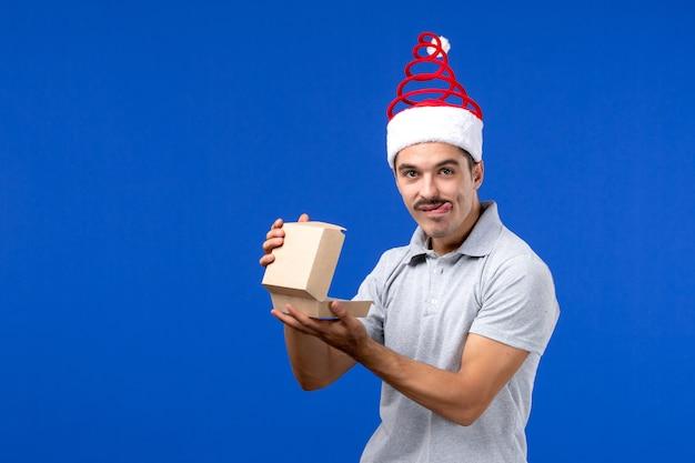 Vista frontal macho joven con paquete de comida en la pared azul trabajo masculino humano servicio de alimentos