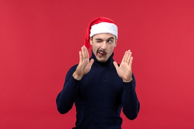 Vista frontal macho joven posando con gorro de año nuevo sobre fondo rojo.