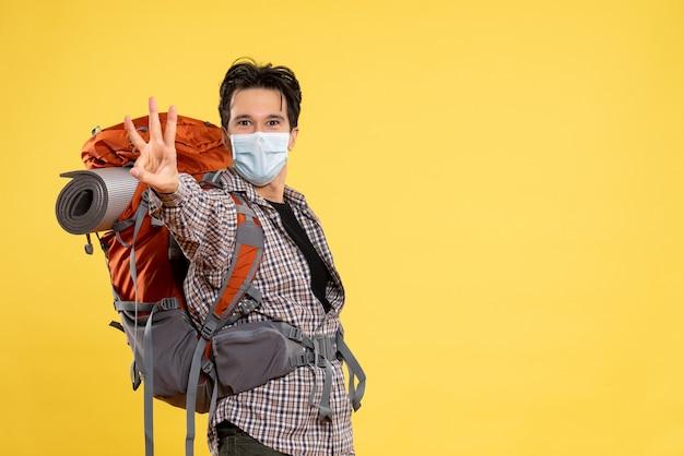 Vista frontal macho joven preparándose para el senderismo en máscara en amarillo