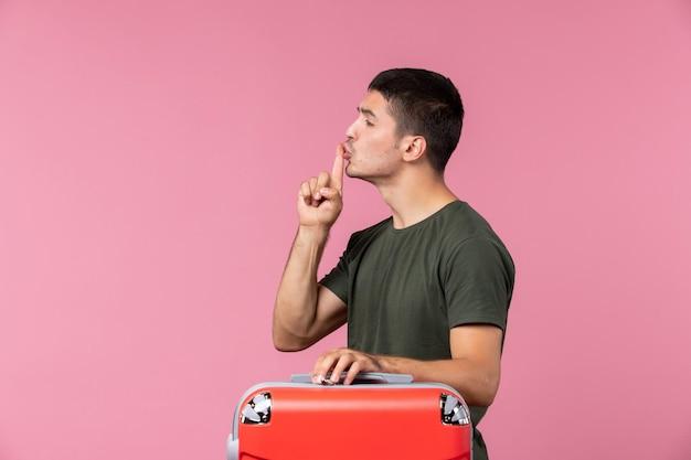 Vista frontal macho joven preparándose para las vacaciones con bolsa en espacio rosa
