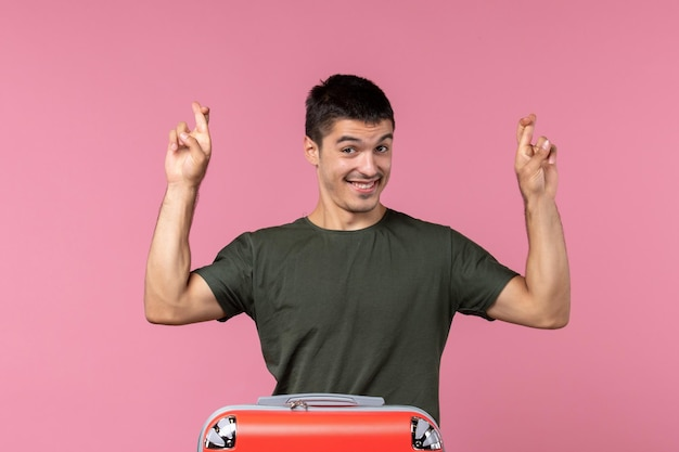 Vista frontal macho joven preparándose para las vacaciones cruzando los dedos en el espacio rosa