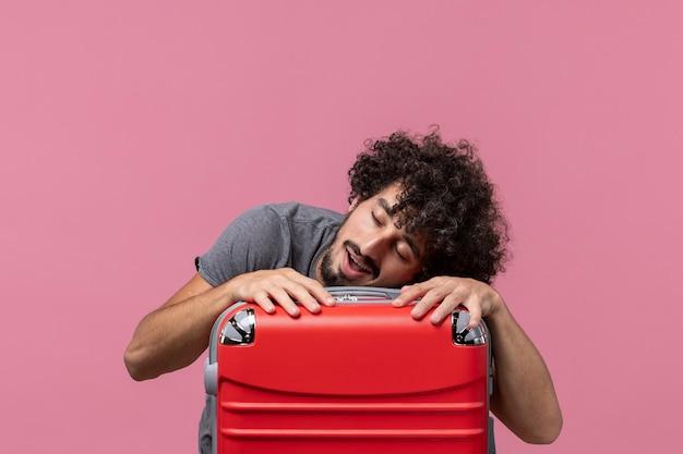Vista frontal macho joven preparándose para las vacaciones y sentirse cansado en el espacio rosa