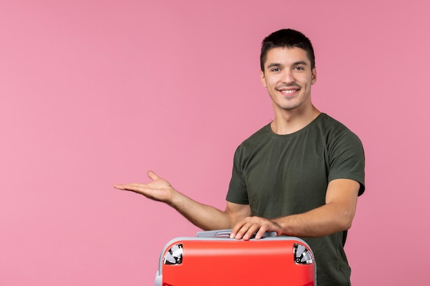 Vista frontal macho joven preparándose para las vacaciones y sintiéndose feliz en el espacio rosa