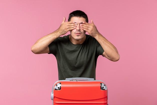 Vista frontal macho joven preparándose para las vacaciones y tapándose los ojos en el espacio rosa