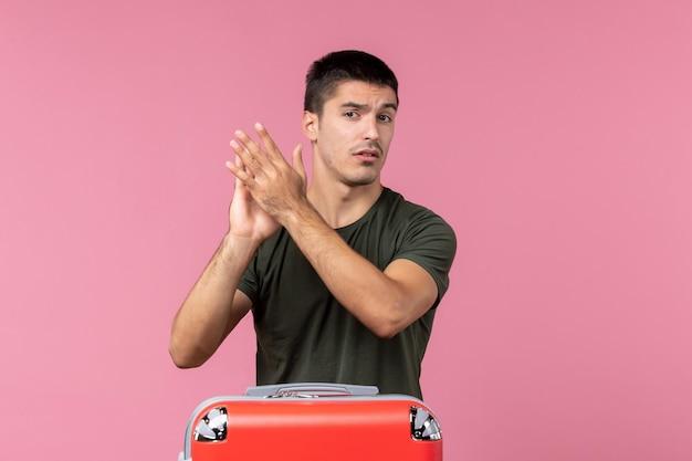 Vista frontal macho joven preparándose para viaje aplaudiendo en espacio rosa