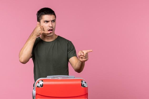 Vista frontal macho joven preparándose para viaje con bolsa roja en espacio rosa