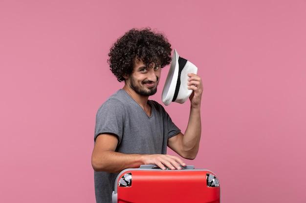 Vista frontal macho joven preparándose para el viaje y sosteniendo el sombrero en el espacio rosa