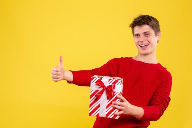Vista frontal macho joven con regalo de navidad en piso amarillo regalo año nuevo emoción humana color navidad