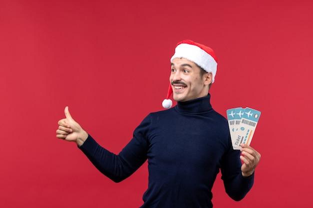 Vista frontal macho joven sosteniendo billetes de avión sobre fondo rojo claro