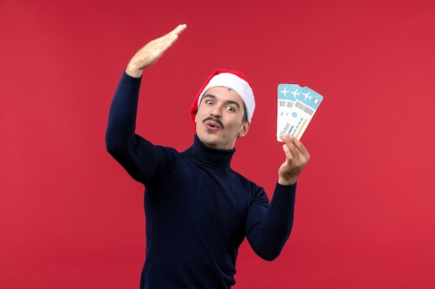 Vista frontal macho joven sosteniendo billetes de avión sobre el fondo rojo.