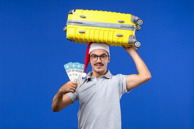 Vista frontal macho joven sosteniendo boletos y una bolsa pesada en el avión de vacaciones de vuelo de fondo azul