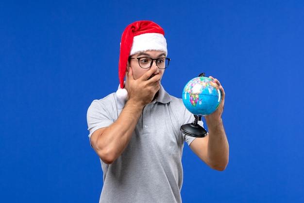 Vista frontal macho joven sosteniendo el globo terráqueo en la pared azul viaje de vacaciones en avión humano