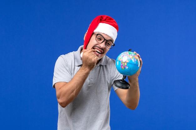 Vista frontal macho joven sosteniendo globo terráqueo en la pared azul viaje vacaciones en avión humano