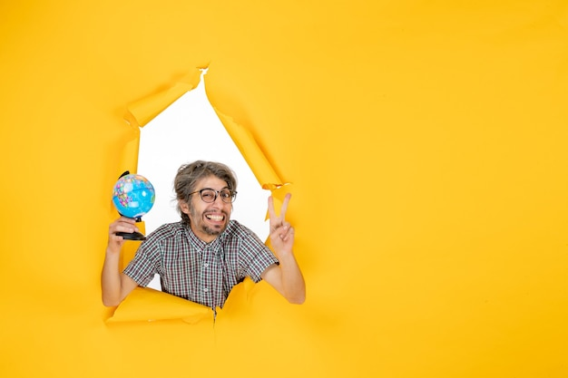 Vista frontal macho joven sosteniendo globo terráqueo sobre fondo amarillo color navidad planeta vacaciones mundo país