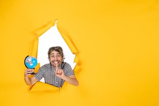 Vista frontal macho joven sosteniendo el globo terráqueo sobre el fondo amarillo emoción planeta navidad vacaciones país mundo color