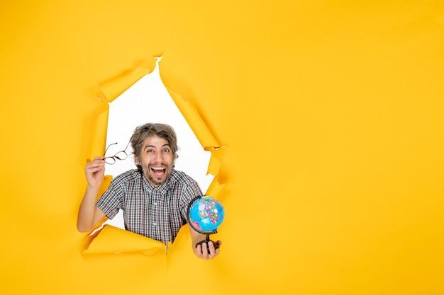 Vista frontal macho joven sosteniendo globo terráqueo sobre fondo amarillo planeta vacaciones de navidad mundo país emoción color
