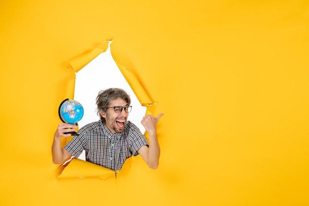 Vista frontal macho joven sosteniendo globo terráqueo sobre fondo amarillo vacaciones mundiales emoción navidad país colores planeta