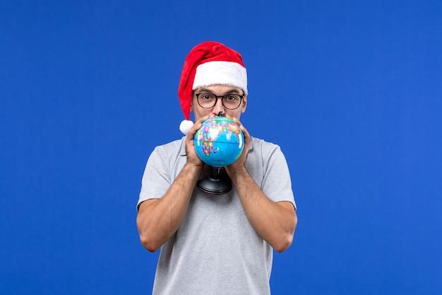 Vista frontal macho joven sosteniendo globo terráqueo sobre pared azul avión viaje de vacaciones macho